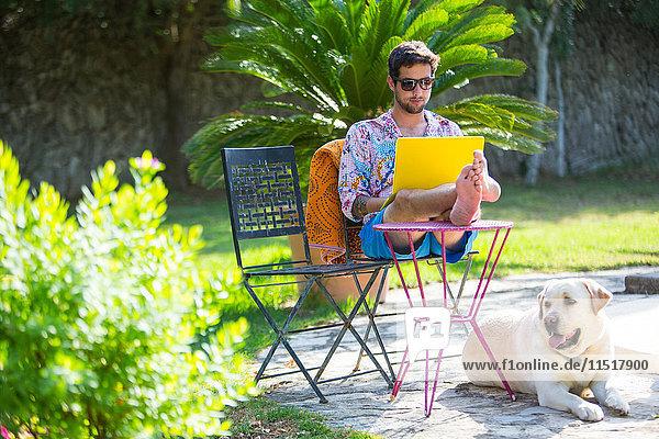 Mann mit erhobenen Füßen am Laptop-Computer