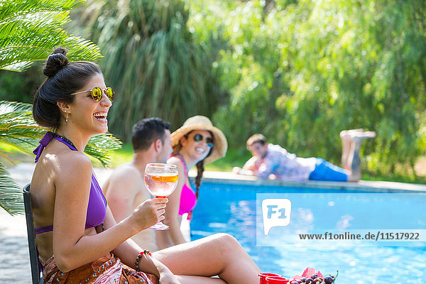 Freunde am Pool bei einem Drink