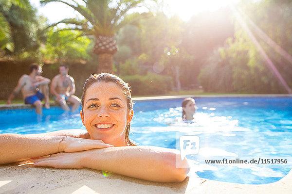 Frau im Schwimmbad ruht sich am Beckenrand aus und schaut lächelnd in die Kamera