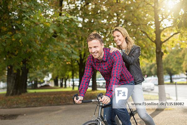 Romantisches Paar mittlerer Erwachsener radelt im Stadtpark