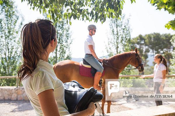 Weiblicher Stallbursche trägt Sattel in ländlichen Ställen
