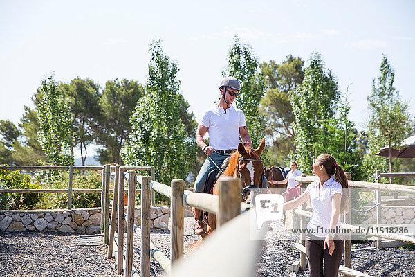 Stallknechtin führt Reiterin auf der Koppel eines ländlichen Reiterhofes
