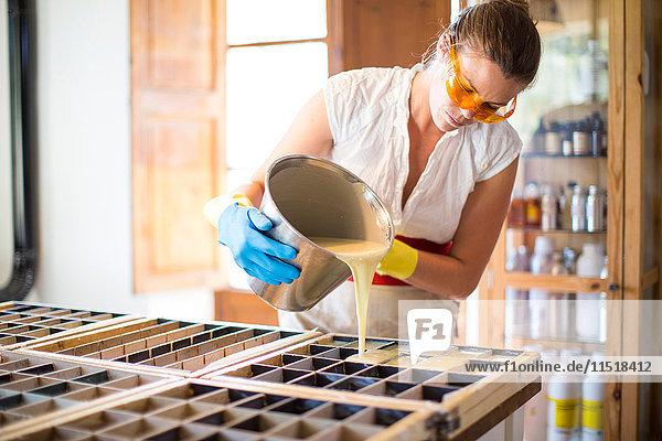 Junge Frau gießt in einer Werkstatt für handgemachte Seife Flüssigkeit in eine Seifenform