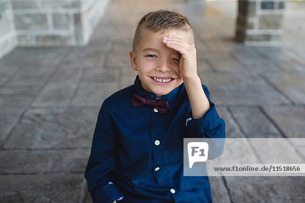 Portrait of boy shielding eyes looking at camera smiling