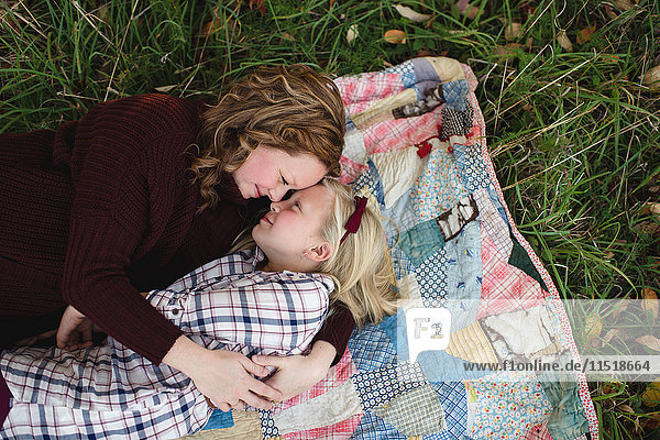 Mother and daughter lying on blanket face to face hugging