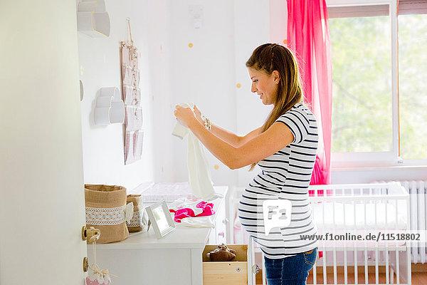 Schwangere Frau im Kinderzimmer bereitet Babykleidung vor Schwangere Frau im Kinderzimmer bereitet Babykleidung vor