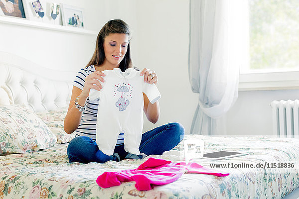 Pregnant woman sitting on bed looking at baby clothes