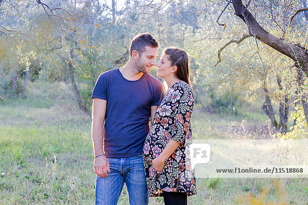 Pregnant couple in forest face to face smiling