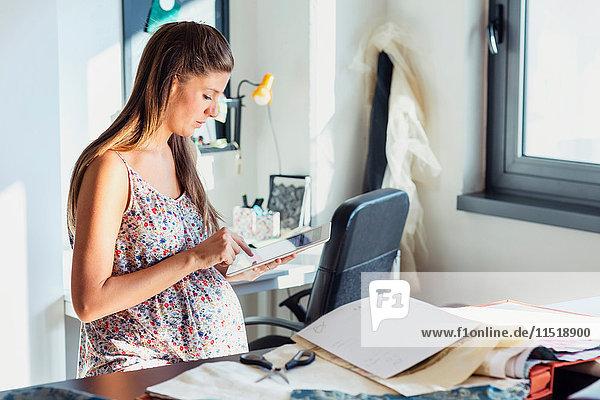 Schwangere Frau im Büro mit digitalem Tablett