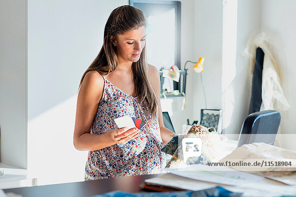 Pregnant woman looking at swatches and fabric samples