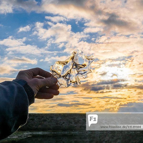 Menschenhand hält Eis gegen den Himmel  Ural  Russland