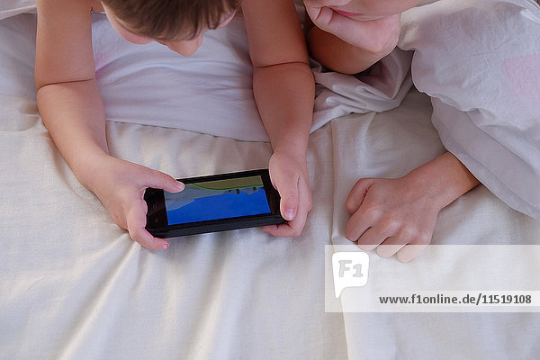 Kinder spielen ein Spiel auf dem Handy im Bett