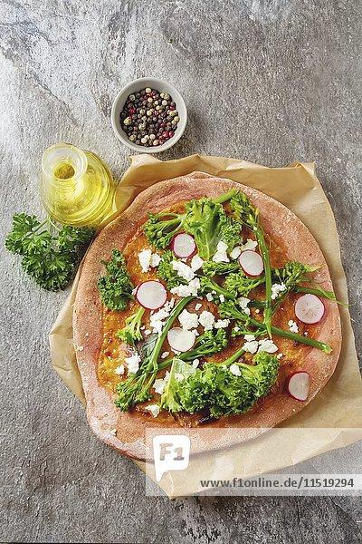 Pizza aus Rote-Bete-Teig mit Brokkoli  Salat  Radieschen und Feta  daneben Olivenöl  Pfeffer und Petersilie