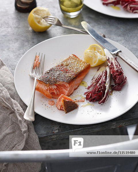 Crispy skin trout with lemon and radicchio on plate  close-up