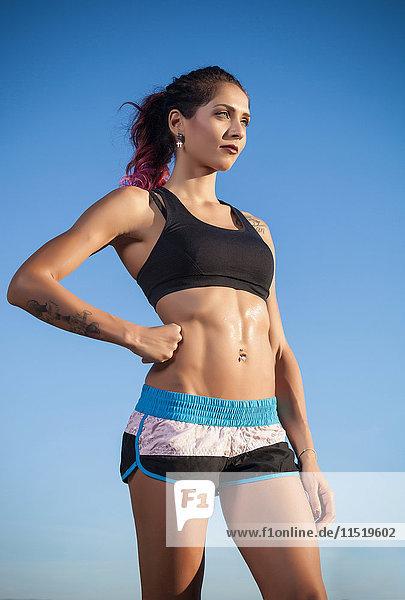 Porträt einer jungen Frau in Sportkleidung  Hand auf der Hüfte  im Freien