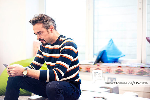 Businessman sitting in office reading smartphone texts