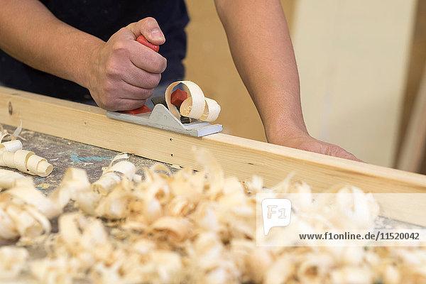 Hand eines männlichen Tischlers mit Holzhobel in der Werkstatt
