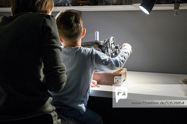 Rückansicht eines Jungen mit Mutter  die lernt  den Griff einer Nähmaschine zu drehen