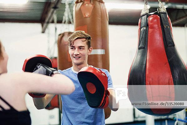 Female boxer training  punching teammate's punch mitt