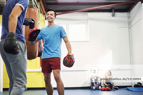 Male boxers training  in boxing gloves and punch mitts