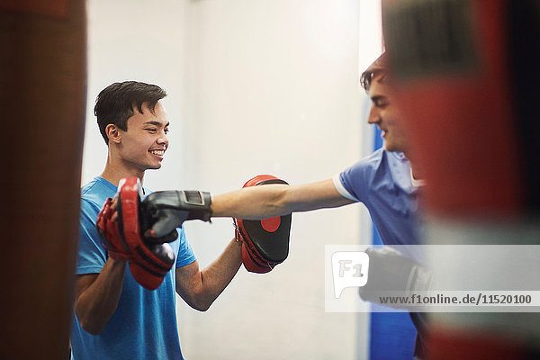 Male boxer training  punching teammate's punch mitt