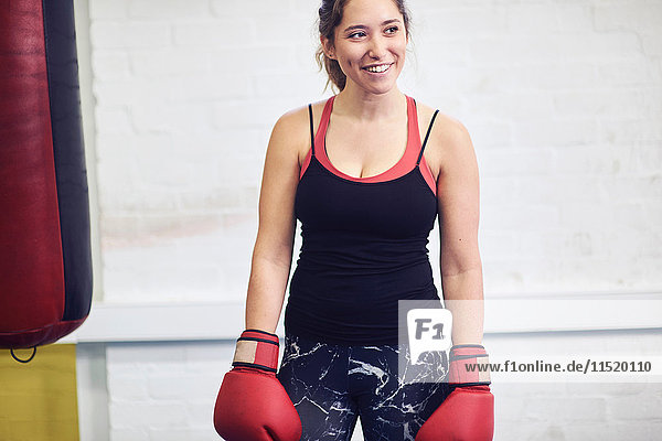 Young female boxer wearing red boxing gloves