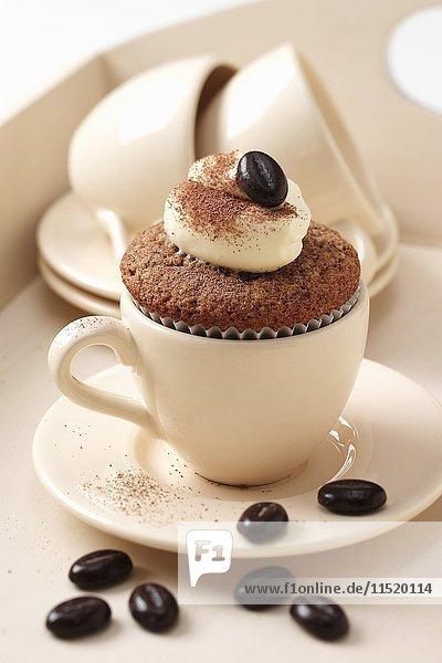 Cappuccino-Cupcake in Espressotasse mit Schokoladenbohnen