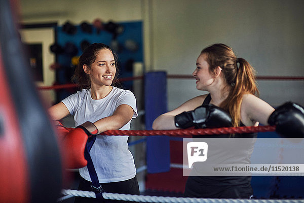 Young female boxers leaning against boxing ring ropes chatting