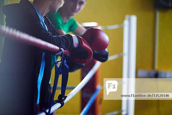 Young male boxers leaning against boxing ring ropes