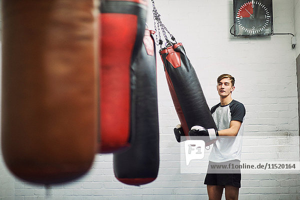 Young male boxer lifting punch bag in gym