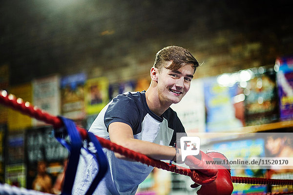 Portrait of young male boxer leaning against boxing ring ropes