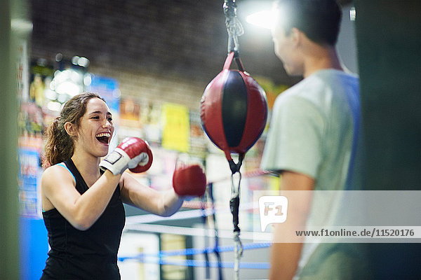 Young female boxer punching speed bag in gym