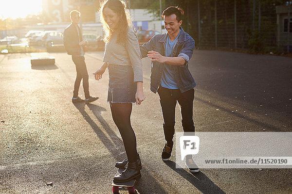 Junger Mann schiebt junge Skateboarderin auf sonnenbeschienener Straße