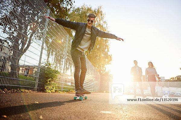 Young male skateboarder skateboarding on sunlit street