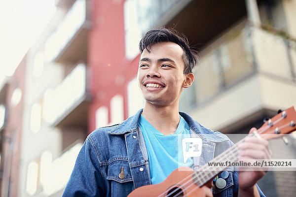 Young man on street playing ukulele