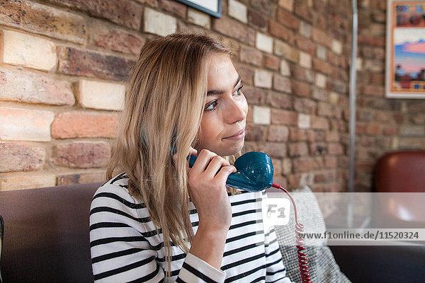 Junge Frau sitzt zu Hause und telefoniert