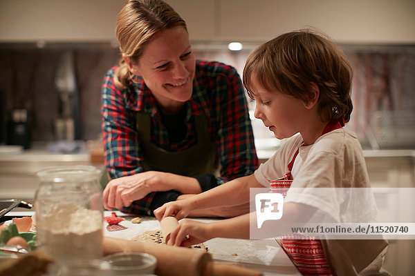 Mature woman and son rolling dough on kitchen counter