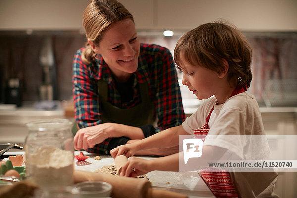 Reife Frau und Sohn rollen Teig auf der Küchentheke