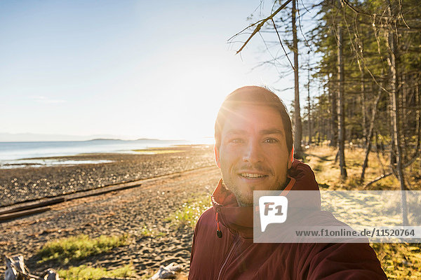 Sunlit portrait of man at Rathrevor Beach Provincial Park  Vancouver Island  British Columbia  Canada