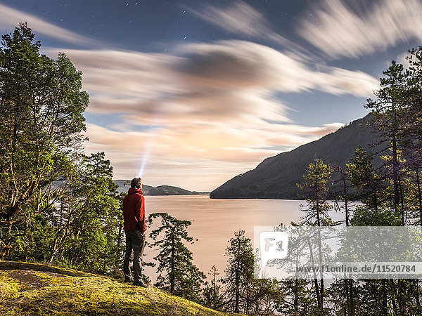 Male hiker looking up at evening stars  Comox Lake  Courtenay  Vancouver Island  British Columbia  Canada