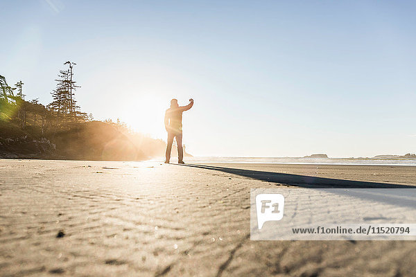 Man photographing from Long Beach at sunrise  Pacific Rim National Park  Vancouver Island  British Columbia  Canada