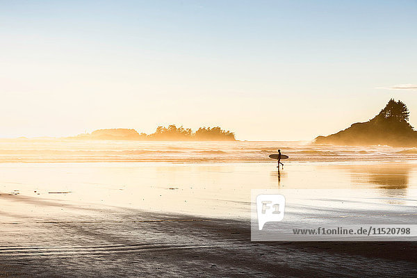 Male surfer carrying surfboard on Long Beach  Pacific Rim National Park  Vancouver Island  British Columbia  Canada