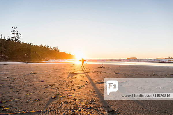 Man dancing on Long Beach at sunset  Pacific Rim National Park  Vancouver Island  British Columbia  Canada