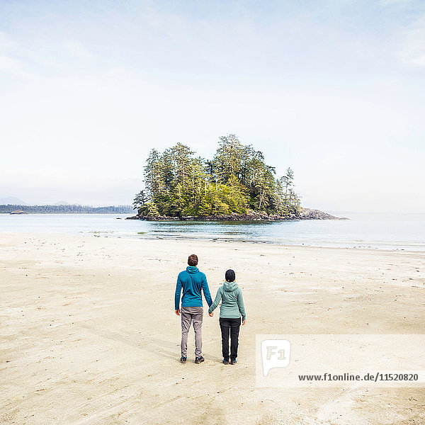 Couple looking out at island from Long Beach  Pacific Rim National Park  Vancouver Island  British Columbia  Canada