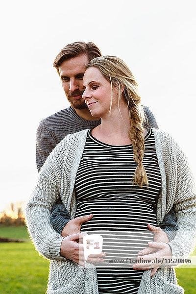 Mann umarmt und berührt den schwangeren Bauch seiner Freundin in Feldlandschaft