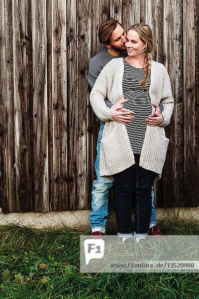 Mann küsst schwangere Freundin am Holzzaun auf die Wange