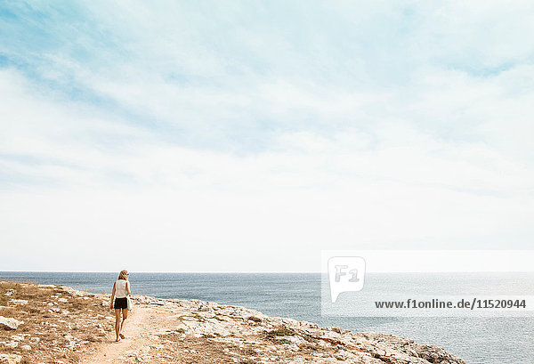 Woman walking on cliff  Menorca  Spain