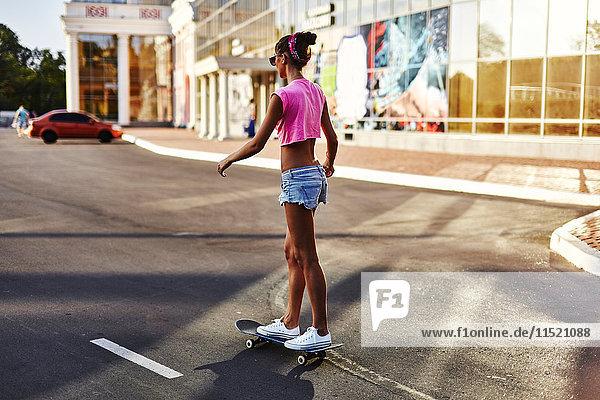 Junge Frau beim Skateboarden entlang der Straße  Rückansicht