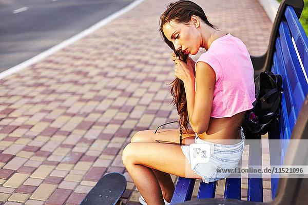 Junge Frau sitzt auf Bank  fixiert Haare  Skateboard auf dem Boden neben ihr
