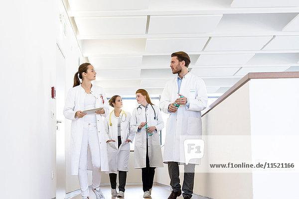 Male and female doctors walking in hospital corridor  talking